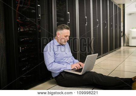 Technician using laptop to analyse server at the data centre