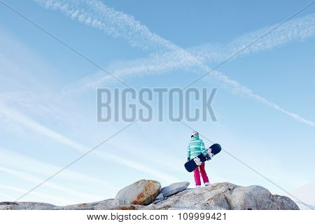 Back view of female snowboarder wearing colorful helmet, blue jacket, grey gloves and pink pants standing on rocks with snowboard in one hand against X sign on sky - winter sports concept