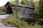 pic of covered bridge  - covered bridge in vermont with a green roof during the autumn season - JPG