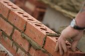 stock photo of bricklayer  - Bricklayer setting bricks on a construction site