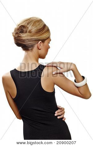 beautiful woman wearing hair in french roll updo in sexy black dress standing with her back against white background .