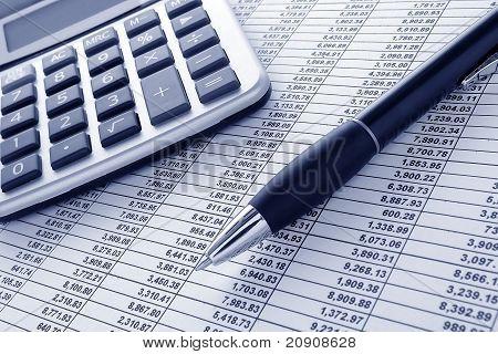 Pluma y calculadora en hoja de cálculo financiero