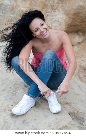 Young Smiling Woman Lacing Up Shoes