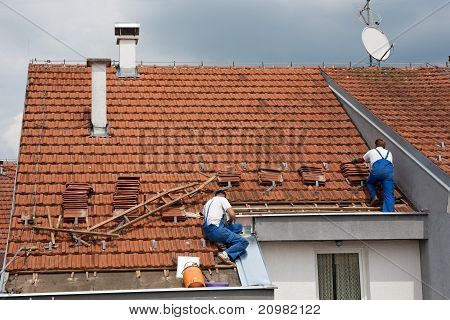 Two Men Working On The Roof