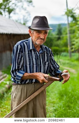 Old Rural Man Sharpening Scythe