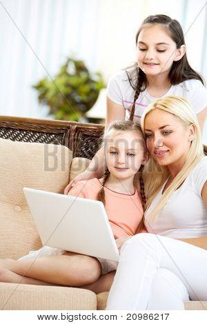 Mulher bonita e suas duas filhas, sentado no sofá e olhando para a tela do laptop