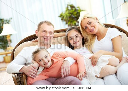 Portrait of happy parents with two girls sitting on sofa
