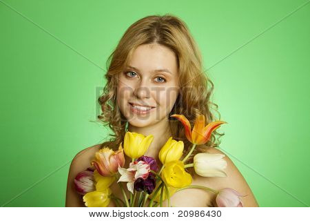 Happy Young Woman hugging a bouquet of tulips
