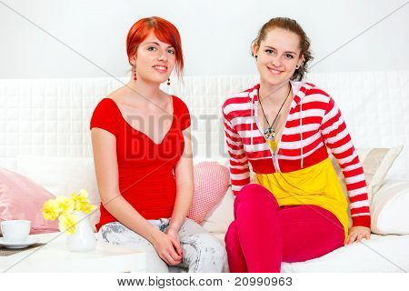 Two smiling young girlfriends sitting on sofa at living room