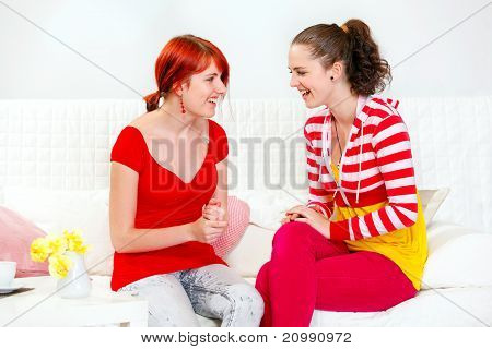 Two laughing young girlfriends sitting on sofa and looking each other