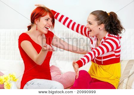 Two happy young girlfriends sitting on sofa and cheerfully embracing