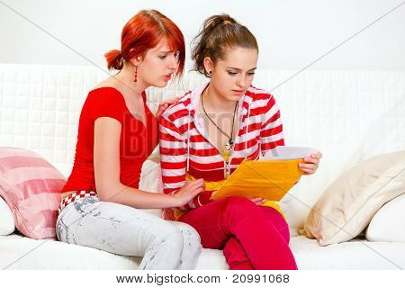 Attentive young girl soothing reading letter with bad news girlfriend