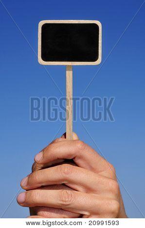 somene holding a blank blackboard label over the sky