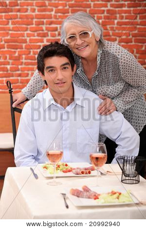 a young man and an old woman at the restaurant posing for the camera