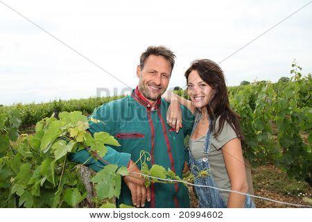 Happy couple of winegrowers in vineyard