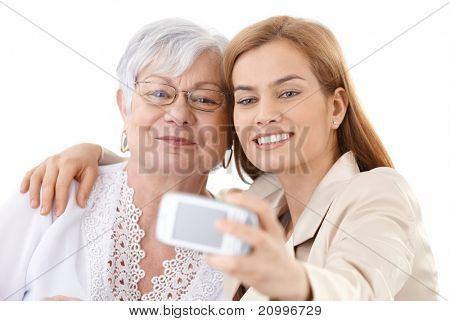 Senior mother and attractive daughter hugging each other, taking photo of themselves by digital camera, smiling happily.?