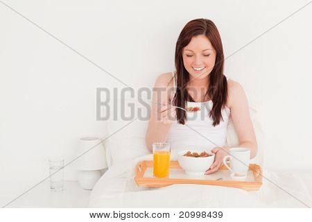 Beautiful red-haired female having her breakfast while sitting on her bed