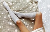 winter, clothes, fashion and people concept - close up of young woman legs in knee socks on bed over poster