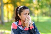 Woman Blowing Her Nose On A Tissue Outdoors poster