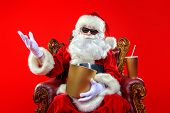 Merry Christmas and Happy New Year. Santa Claus sitting on his armchair and eating popcorn and drink poster