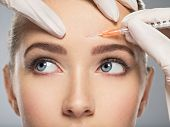 Portrait of young Caucasian woman getting cosmetic injection in forehead. Beautiful woman gets botox poster