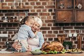 Grandmother And Granddaughter Embracing On Kitchen poster