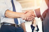 Businessmen shaking hands during a meeting. Closeup of business handshake between two colleagues in  poster