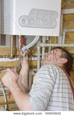 Plumber at work. Servicing gas boiler