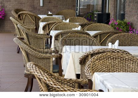 Outdoor cafe. Row of rattan chairs and tables