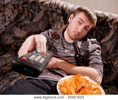 Hombre soñoliento con cerveza y patatas fritas en casa viendo la televisión