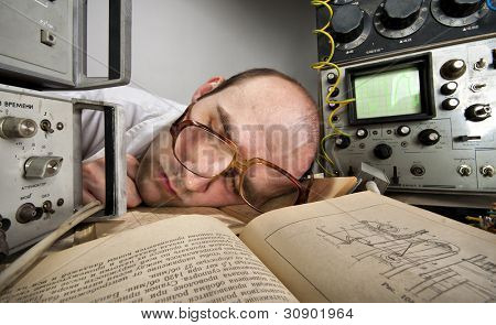 Exhausted scientist sleeping on book at vintage technological laboratory