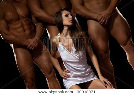 Beautiful young woman against three athletes in darkness