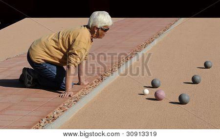 Senior Woman Studium Boccia Kugeln auf Sand-Hof