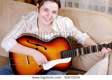 Smiling Teenage Girl Playing By Guitar