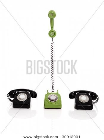 Green phone ringing in the midle of two black phones, isolated on white background