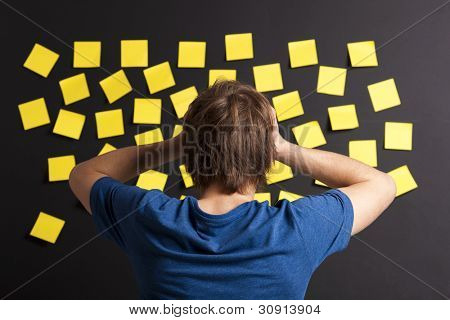 Young student with stress and looking to a board full of yellow notes
