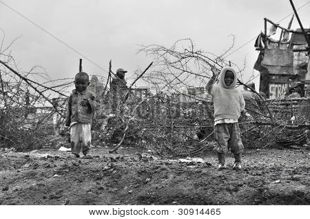 Unidentified kids walk in mud through the Nairobi slum