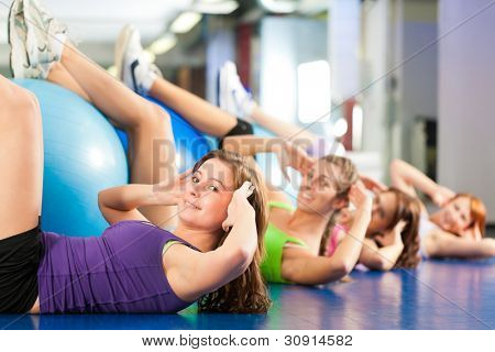 Fitness - Young women doing sports training or workout with gymnastic ball in a gym