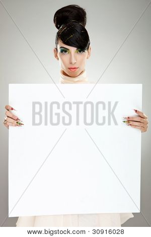 Closeup of young, pretty fashion woman in dress standing near huge blank board and holding it. Lots of copyspace for your text and logo