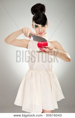 fashion woman in nice dress with colorful makeup and big finger nails, cutting a heart with a big kitchen knife