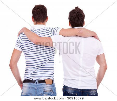 back view of two friends  standing embraced and looking at something on white background