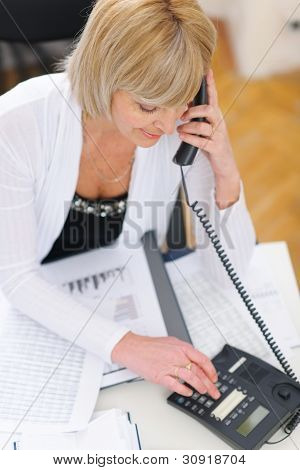 Senior Business Woman Making Phone Calls At Office