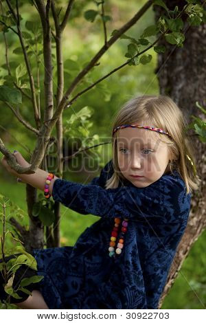 Little Girl Sitting On A Branch Of An Apple Tree