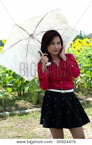 Portrait Of Pretty Asian Woman Hold White Umbrella Posing In Sunflower Field .