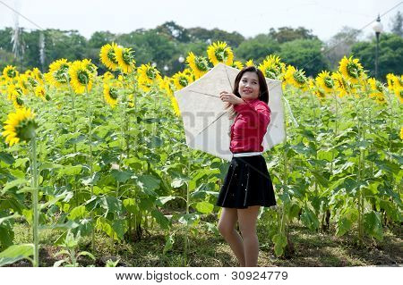 Pretty Asian Woman In Red Dress Hold Umbrella Is Joyfully  In Sunflower Field .