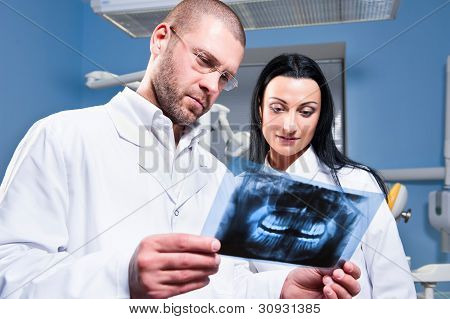 Dentist And Assistant Checking X-ray At Dental Clinic