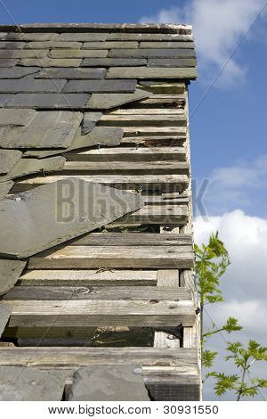 Storm Damaged Roof With Lots Of Missing Slates