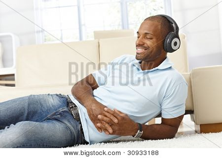 Handsome black man enjoying listening to music on headphones, lying on living room floor, smiling with eyes closed.