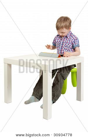 Boy With A Tablet Pc On The Desk