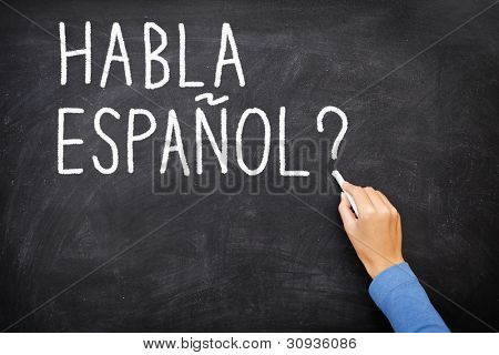 "Spanish language learning concept image. Teacher or student writing ""habla espanol"" on blackboard during spanish language course class."